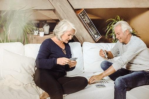 Stariji par sa zaušnim slušnim pomagalima pri kartanju