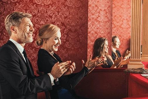 Muškarac i žena sa zaušnim slušnim pomagalima u operi