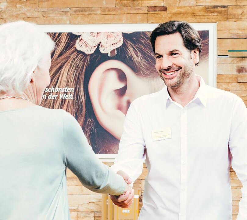 Mann im Fachinstitut begrüßt Frau zur Hörgeräteberatung